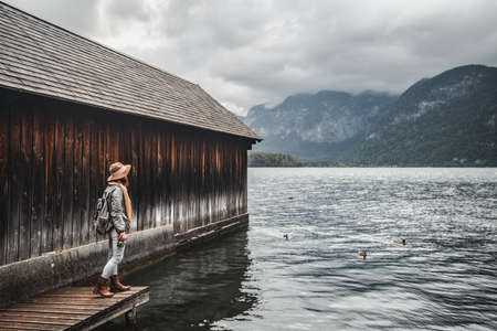 Young tourist on a wooden pier by the lake
