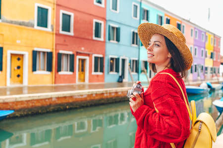 Beautiful young girl with a retro camera in Burano