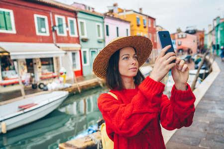 Beautiful tourist takes photos in Burano