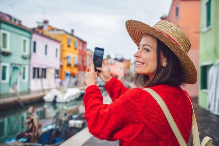 Smiling tourist takes photos in Burano