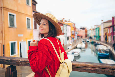 Smiling beautiful girl in a straw hat in Burano