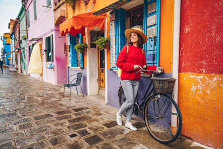 Smiling young girl with a bike in Italy
