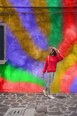 Smiling young girl on the background of a colored wall Stock Photo
