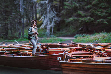Young woman with a retro camera in a wooden boat