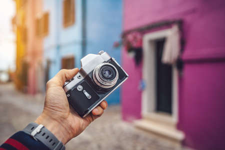 Photographer holding a retro camera in Burano closeup