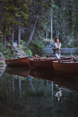 Young photographer with a retro camera in a wooden boat Stock Photo