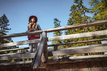Young woman with a retro camera on the bridge Stock Photo