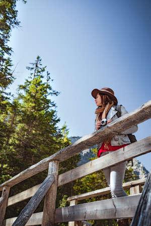 Attractive woman with a retro camera on a wooden bridge