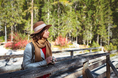 Young woman with a retro camera on a wooden bridge