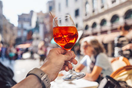 Man's hand with a glass of aperol in Venice