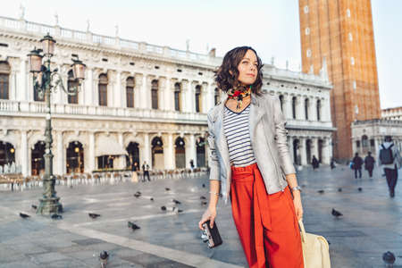 Attractive girl with a retro camera on the Piazza San Marco