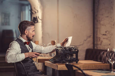 Young man with a retro typewriter in a restaurant