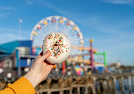 Female hand holding a donut on a background of a ferris wheel in Los Angeles Banque d'images