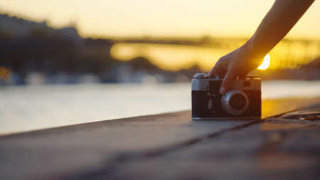 Young photographer with a retro camera at sunset, close-up