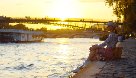Young girl by the river at sunset in Paris, France