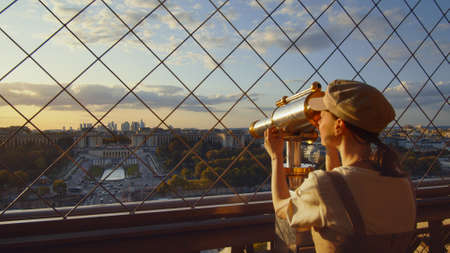 Young tourist looking through binoculars at the view point, Paris