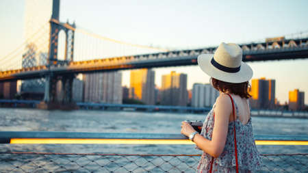 Young woman with a retro camera at the Manhattan Bridge in New York Фото со стока - 153447734