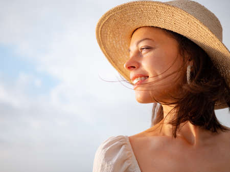 Smiling young woman in a hat outdoors