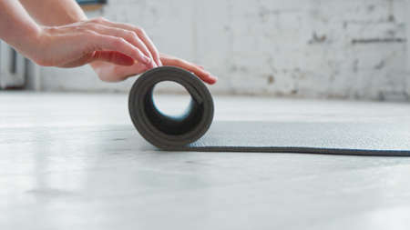 Woman hands roll gray rubber mat to train on parquet floor in spacious light yoga studio extreme close view