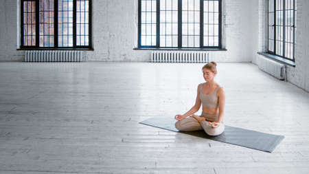 Smiling blonde woman in stylish tracksuit sits on mat in lotus posture meditating in light spacious studio with large windows