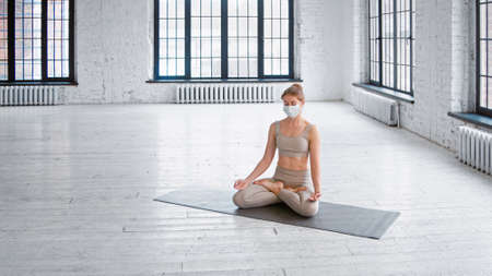 Tranquil young woman in tracksuit and protective mask meditates sitting in lotus pose in spacious studio with large windows