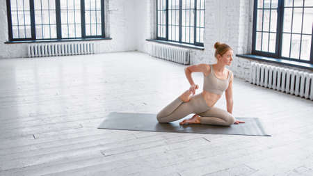 Pretty young lady yoga practitioner with hair bun in beige tracksuit does pigeon pose on floor near window in studio side view Фото со стока