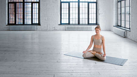 Slim young female yoga practitioner in light gray tracksuit sits on mat in lotus pose meditating in empty spacious studio