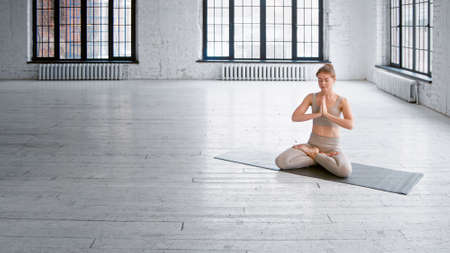 Athletic barefoot lady in tracksuit sits on mat in lotus pose with namaste mudra meditating in spacious studio with windows