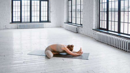 Young flexible lady trainer in stylish tracksuit does head to knee forward bend sitting on mat in yoga studio with white windows