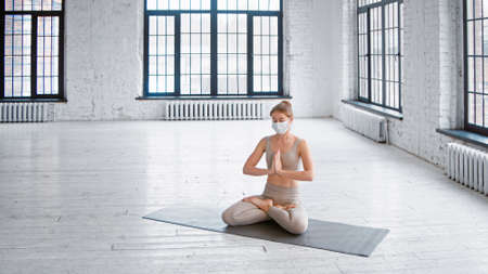 Pretty young sportswoman in tracksuit and protective mask meditates sitting in lotus pose with namaste in spacious studio