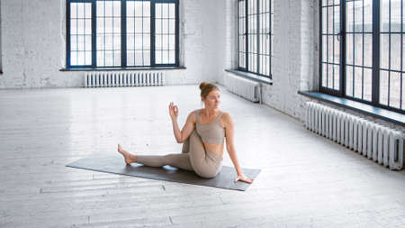 Flexible blonde lady in stylish light gray tracksuit does half lord of fishes pose sitting on mat in studio with large windows Фото со стока