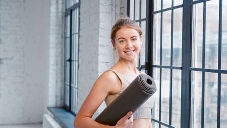 Blonde woman fitness trainer with hair bun holding mat looks out of window and turns to camera in modern yoga studio closeup