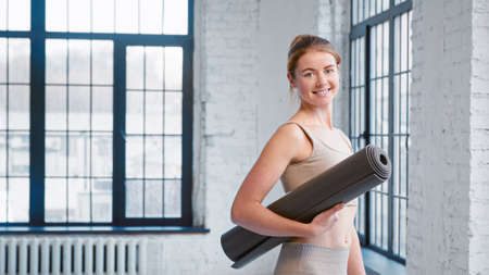 Young female fitness trainer with bun hairstyle holding rolled mat smiles to camera standing by window in modern yoga studio