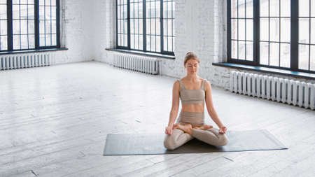 Peaceful young woman in stylish tracksuit sits on mat in full lotus yoga pose meditating in spacious gym Фото со стока