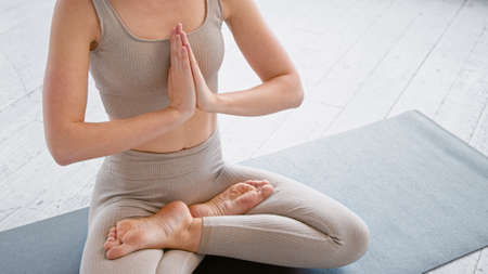 Motion past lady yoga practitioner in new beige tracksuit sitting in lotus position with namaste on mat in light studio closeup Фото со стока