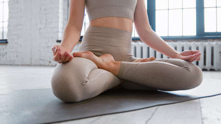 Pretty relaxed young woman in sportswear does yoga breathing exercises sitting in full padma asana in spacious studio close view Фото со стока