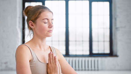Blonde lady with closed eyes in beige top breathes deeply holding hands in namaste mudra by chest in light yoga studio closeup