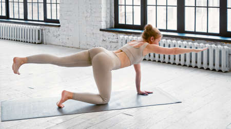 Blonde young yoga teacher with bun hairstyle in tracksuit stands in tiger pose on floor near window in light studio side view Фото со стока