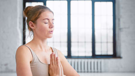 Calm young woman with hair bun in beige top does yoga breathing exercises holding hands in namaste mudra in studio close view
