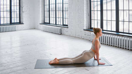 Strong young woman in light beige tracksuit does plank exercise standing on mat near french window in yoga studio side view