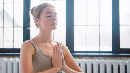 Concentrated woman in beige top prays holding hands in yoga pose namaste mudra by chest in studio closeup