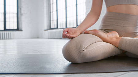 Flexible sportive lady in leggings sits in yoga full lotus position on mat in spacious studio close view space for design