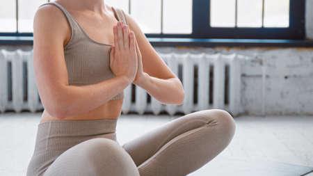 Slim woman in stylish sportswear sits in lotus pose holding hands in namaste mudra on floor in modern yoga studio closeup Фото со стока