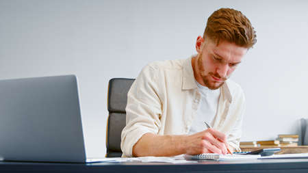 Startup company accountant in yellow shirt summarizes unexpected expenses on calculator and writes into paper notebook at home