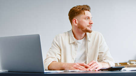 Thoughtful startup manager with beard looks aside and thinks on solving business trouble holding hands on table with laptop