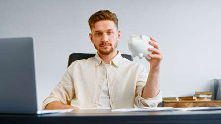 Serious man corporate company manager with beard holds white piggy bank and smiles joyfully posing at office table with laptop Фото со стока
