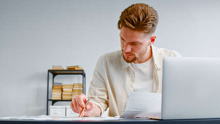 Experienced analyst examines financial reports on paper sheets sitting at table with white laptop against office bookshelf closeup