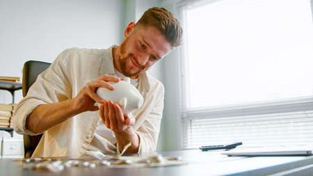 Cheerful guy manager with beard shakes white piggy bank to take last coin over gray table against office window with sunlight Фото со стока