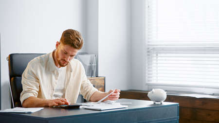 Thoughtful guy manager with beard sums up administrative expenses on calculator and thinks on reducing costs at table in office