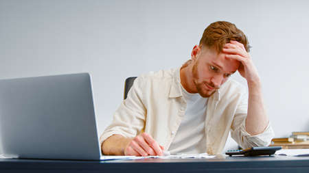 Skilled accountant looks at paper checks and summarizes total on calculator sitting at table with white laptop in bank office